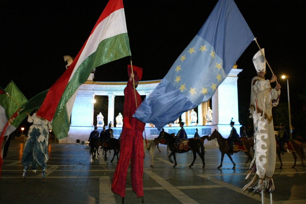 afp. eu-csatlakozás, európai unió - 2004.05.01. Budapest : Hungarian men on stilts dancing with EU and Hungarian flags at the monument of the statues of Hungarian kings at the Heros square of Budapest on Saturday 01 May 2004 as Hungary celebrates the EU e