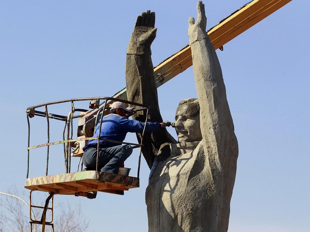 Kazahsztán - közmunkás festi Jurij Gagarin szobrát.