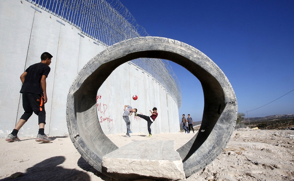 afp.17.10.12 -  Palesztin gyerekek fociznak Ciszjordániában a fal mellett Beit Awa falu közelében