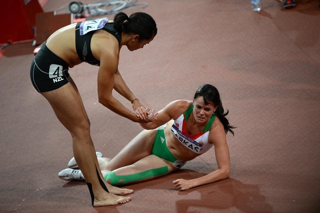 Az új-zélandi Sarah Cowley próbálja felsegíteni a földről a magyar Farkas Györgyit a hétpóbázók utolsó száma, a 800 méteres futás után.A magyar sportoló a 21. helyen végzett a hétpróbázók között.
