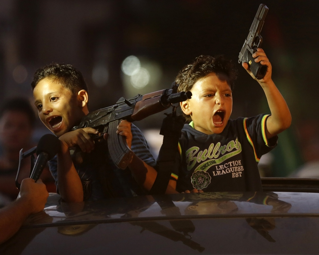 afp. hét képei - Gáza, gyerekek, Children hold up guns (one with an empty magazine) from a car as Palestinians gather in the streets to celebrate after a deal had been reached between Hamas and Israel over a long-term end to seven weeks of fighting in the