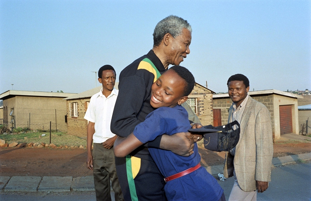 Nelson Mandela nagyítás - SOUTH AFRICA, SOWETO : Anti-apartheid leader and African National Congress (ANC) member Nelson Mandela hugs, on October 4, 1990, a young Sowetan girl as he visits the black township of Soweto (South Western Township) near Johanne