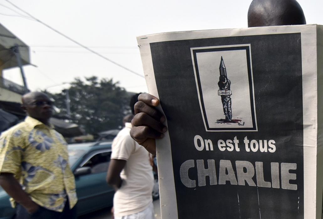 afp. lövöldözés Párizsban, Párizsi vérengzés, Charlie Hebdo, 2014.01.09. IVORY COAST, Abidjan, A man reads on January 9, 2015 the Ivorian satirical weekly L'Elephant in Abidjan, featuring a cartoon about the January 7 massacre in Paris at the Charlie Hebd