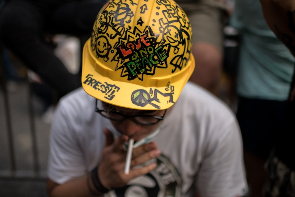 afp. hét képei - Hongkong, Kína, hongkongi tüntetés 2014.10.21. A pro-democracy protester wearing a helmet smokes as he sits next to a barricade opposite the central government offices in the Admiralty district of Hong Kong, after a court injunction order