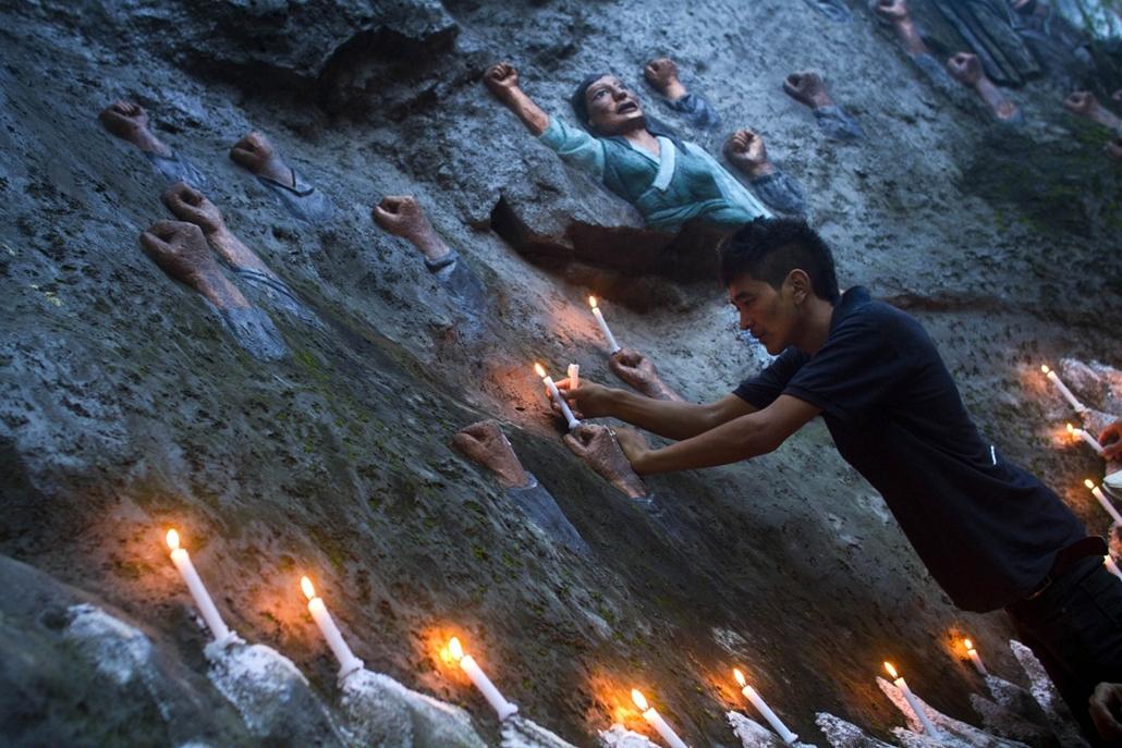 Tibeti férfi gyújt gyertyát egy virrasztás során a mártírhalált halt tibetiek emlékfalánál Indiában. - a hét képei