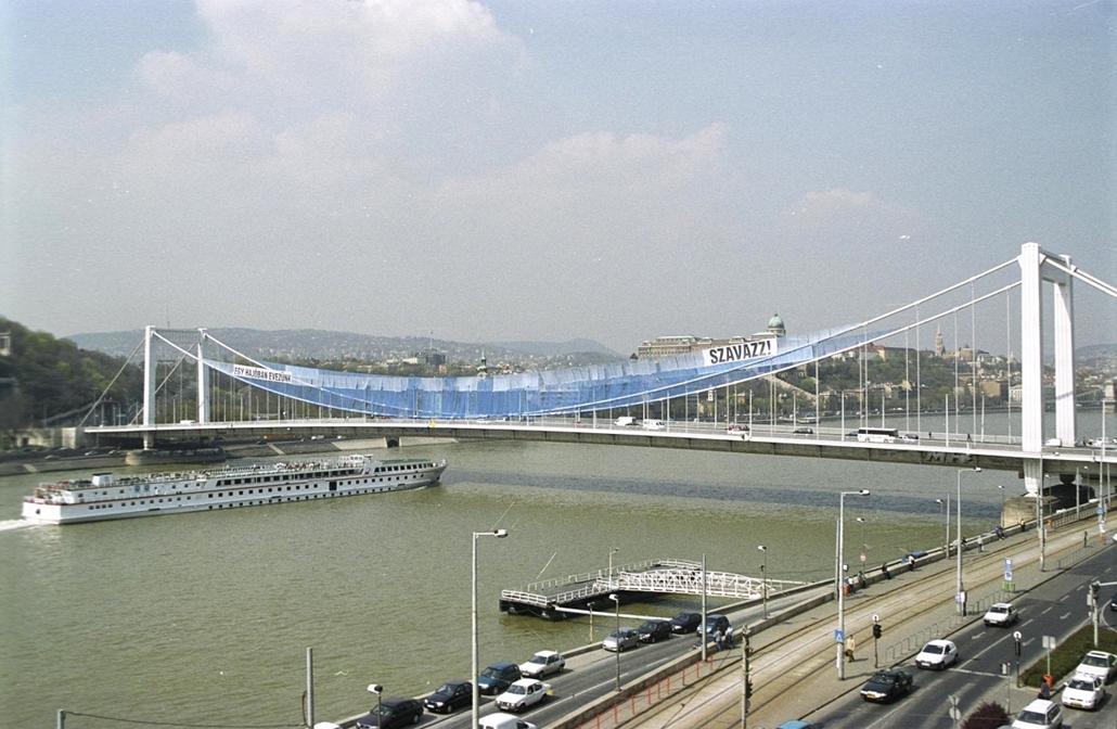 """ba.02.04.02. - ''Hajó a hídon'' - az Erzsébet hídon elhelyezésre kerülő gigantikus méretű (2 x 230m x 45m) képzőművészeti installáció """"Egy hajóban evezünk - Szavazz"""" jelmondattal. A molinó a SuperGroup művészcsoport és a magyarországi Soros Alapítvány seg"""