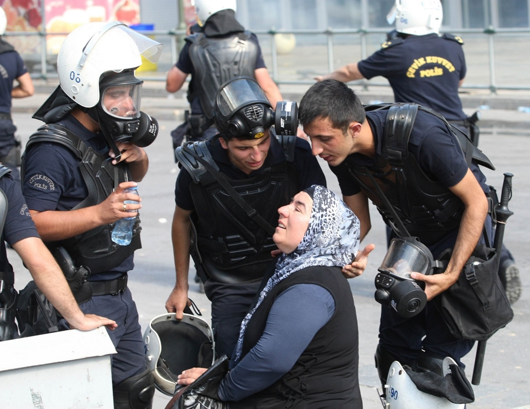 Törökországi tüntetések, 2013, június - Riot police help a woman affected by tear gas on June 1, 2013 during a march to parliament and the prime minister's office in Ankara. Thousands of protesters in Istanbul celebrated a victory on June 1 as police with