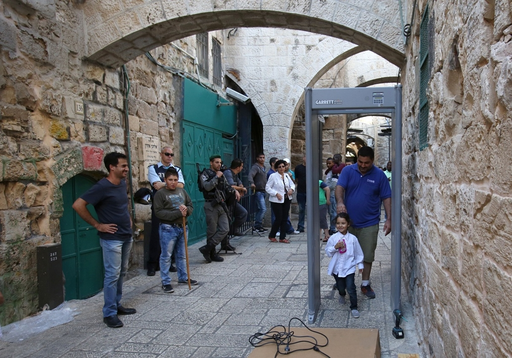 afp.izraeli-palesztin konfliktus 2015 - palesztin támadások Izraelben, Jeruzsálem 2015.10.08. Israeli security forces stand guard as a worker installs a metal detector gate in the Muslim quarter of Jerusalem's Old City on October 8, 2015 following a spate