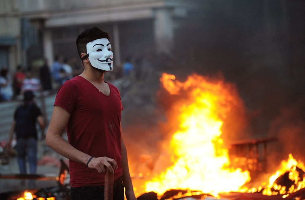 Törökországi tüntetések, 2013, június - A demonstrator wears a Guy Fawkes mask as protestors clash with Turkish riot policemen on May 31, 2013, during a protest against the demolition of the Taksim Gezi Park, in Taksim Square, in Istanbul. Police reported