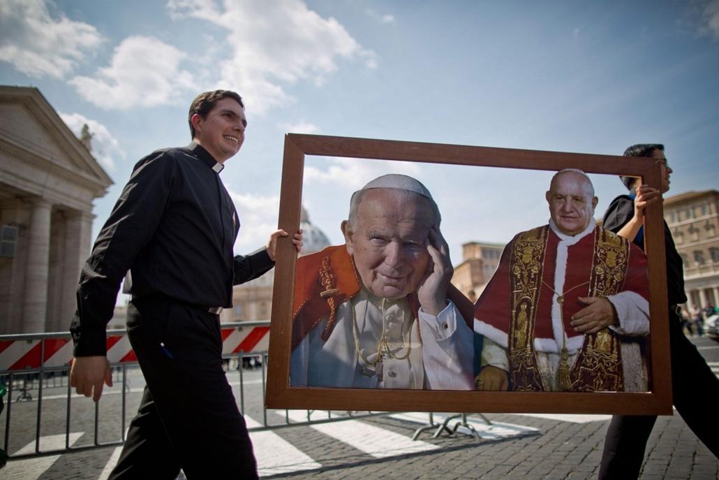 epa. 2014.04.25. Vatikánváros, 2014. április 25. XXIII. János pápa (j) és II. János Pál pápa képét viszik a Krisztus Légionáriusai katolikus kongregáció fiatal papjai a vatikáni Szent Péter térnél 2014. április 25-én. A két pápa szentté avatási ünnepségét