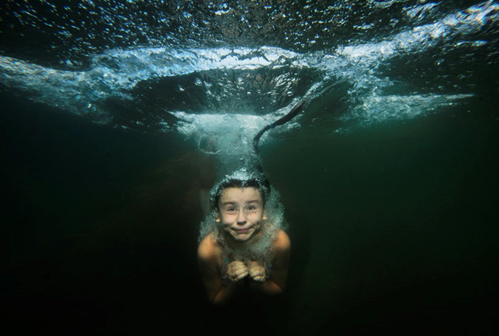 Kislány ugrik be egy tóba Szentpétervár mellett.