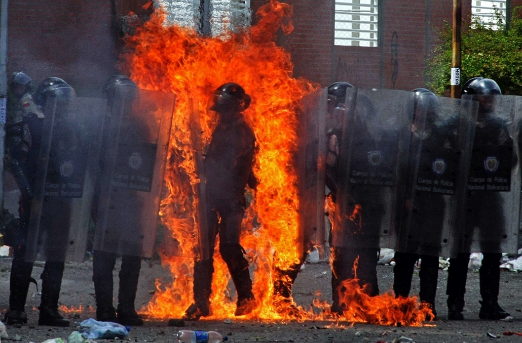 afp. hét képe - 2014.08.25. San Cristobal, Venezuela, molotov-koktél, felgyújtott rendőr - A riot policeman is set on fire by a molotov cocktail thrown by a small group of anti-government protesters during clashes in San Cristobal, Venezuela on August 25,