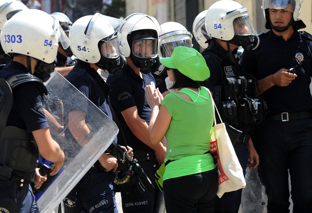 Törökországi tüntetések, 2013, június - A women asks police to stop as Turkish protestors and riot policemen clash on June 1, 2013, during a protest against the demolition of Taksim Gezi Park, in Taksim Square in Istanbul. Police reportedly used tear gas
