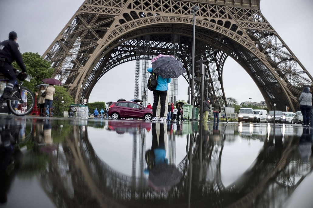Eiffel-torony - Tourists walk under the rain at the feet of the Eiffel Tower on May 16, 2013 in Paris.