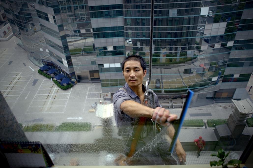afp.14.08.23. Egy kínai dolgozó ablakot tisztít Pekingben