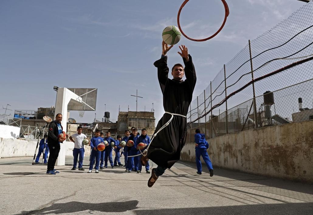 afp.18.03.01. A fereces szerezetes palesztin gyerekekkel kosárlabdázik március 1-jén
