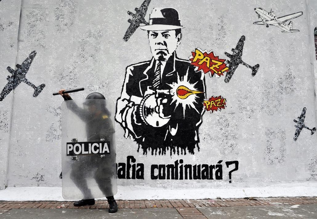 afp.14.04.01. - Bogota, Kolumbia: tüntetés - rendőr a Juan Manuel Santos elnököt ábrázoló graffiti előtt. -  - 7képei