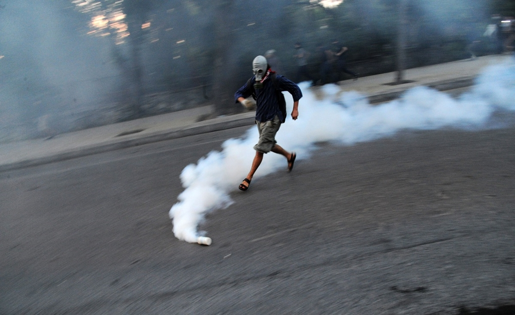 Törökországi tüntetések, 2013, június - A Turkish protestor wearing a gas mask runs towards a gas bomb during clashes early on the morning of May 31, 2013 as part of a protest against the demolition of Taksim Gezi Park, in Taksim Square in Istanbul. Polic