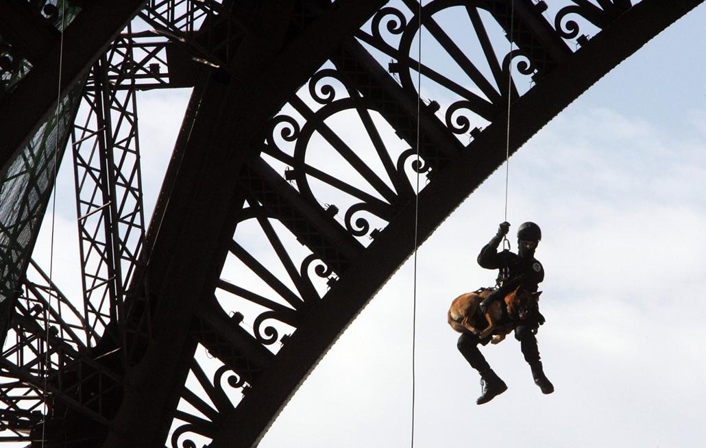 afp. Eiffel-torony 125 éves Nagyítás - 2005.10.08. FRANCE, Paris : Un membre du Raid (Recherche, assistance, intervention, dissuasion) descend la Tour Eiffel en rappel, le 08 octobre 2005 à Paris, lors d'une démonstration à l'occasion de la célébration de