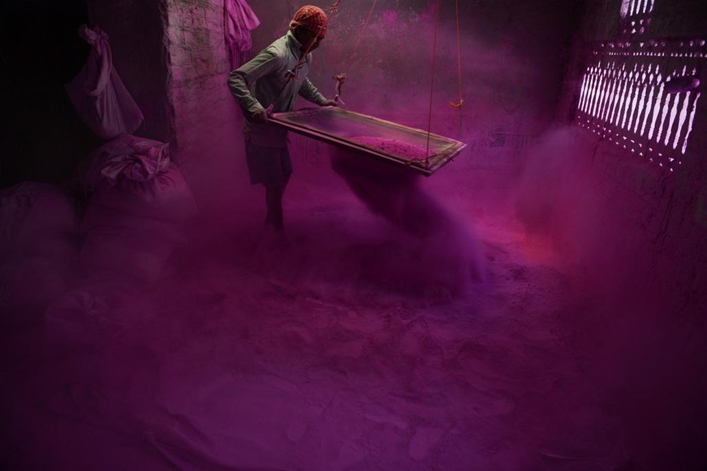 20140315003 - afp.14.03.09. - Siliguri, India: munkás a színek fesztiváljához használt úgynevezett ''gulal'' por szitálása közben.