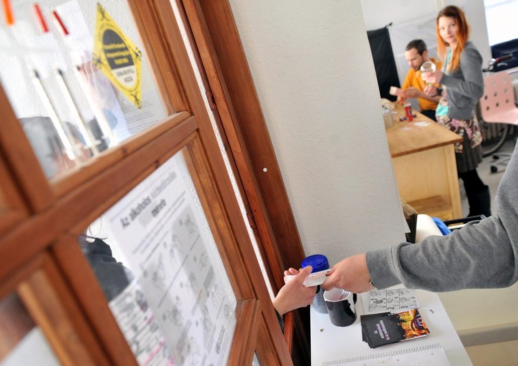mti.13.01.31. - Egy fiatal nő tűket és fecskendőket vesz át Gyékiss Roland programvezetőtől a budapesti Kék Pont Drogkonzultációs Központban 2013. január 31-én.