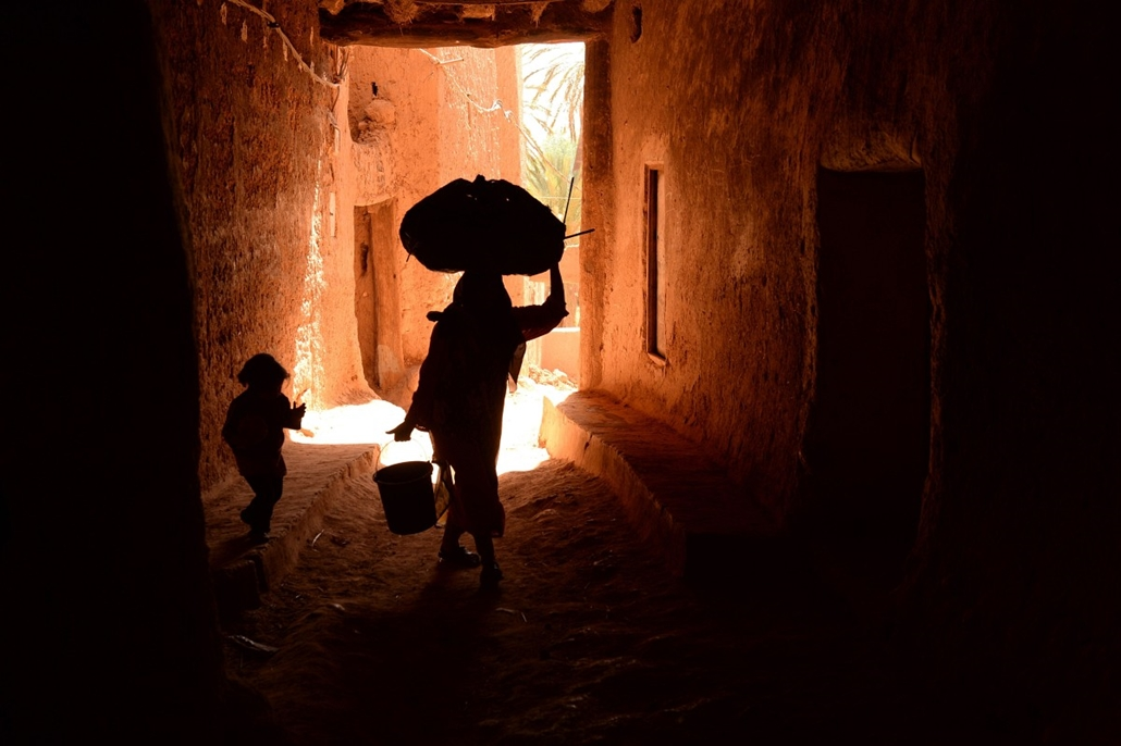 afp. hét képei - Marokkó, 2014.04.21. MOROCCO, Tinghir : A woman carrying a bag on her head walks with her daughter on a street in the old part of the central eastern Moroccan city of Tinghir, on April 21, 2014.