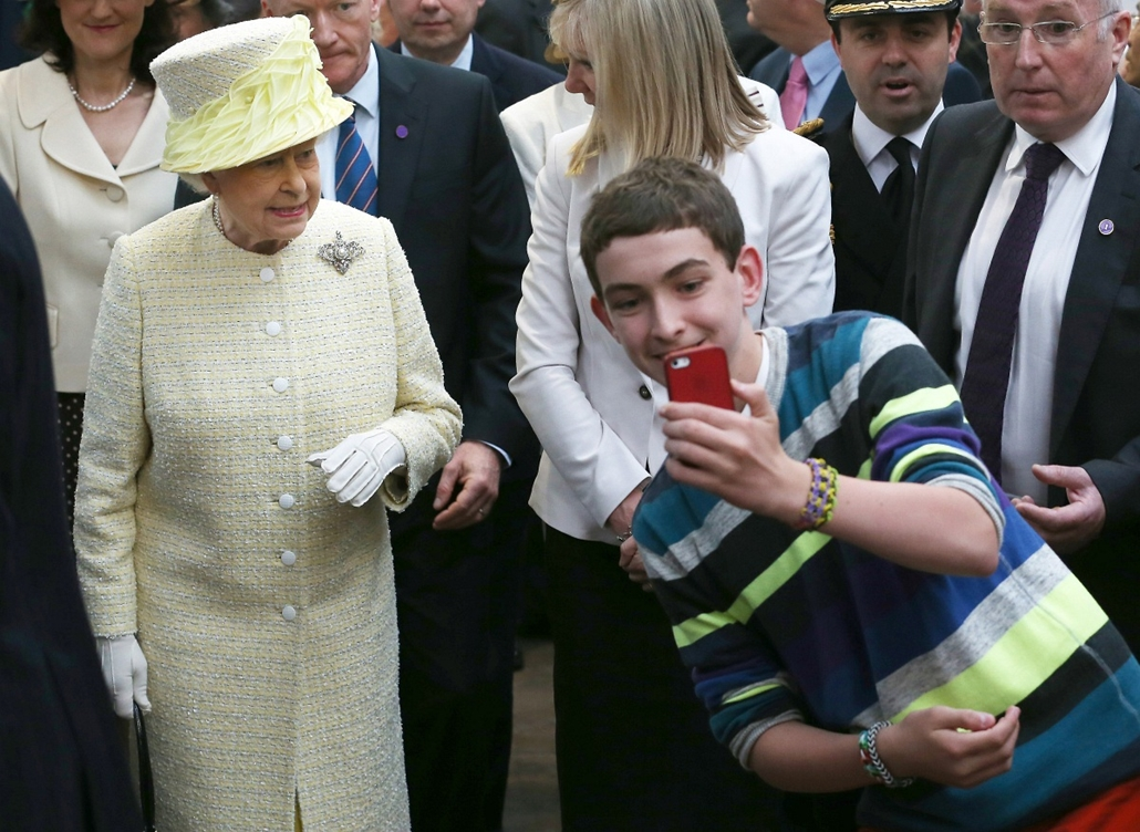 afp. Ezsébet királynő szelfi, selfie, 2014.06.24. UNITED KINGDOM, Belfast : A local youth takes a selfie photograph in front of Queen Elizabeth II during a visit to St George's indoor market on June 24, 2014 in Belfast, Northern Ireland.