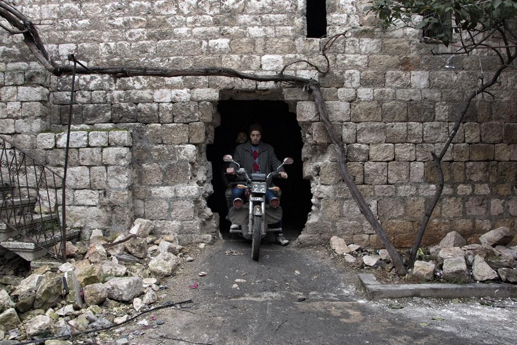 afp.15.01.30. - Aleppo, Szíria: férfiak motoron. A helyi lakosok egy része ilyen járatokon át közlekedik a városban, elrejtőzve ezzel az orvlövészek fegyverei elől. - 7képei, orvlövész