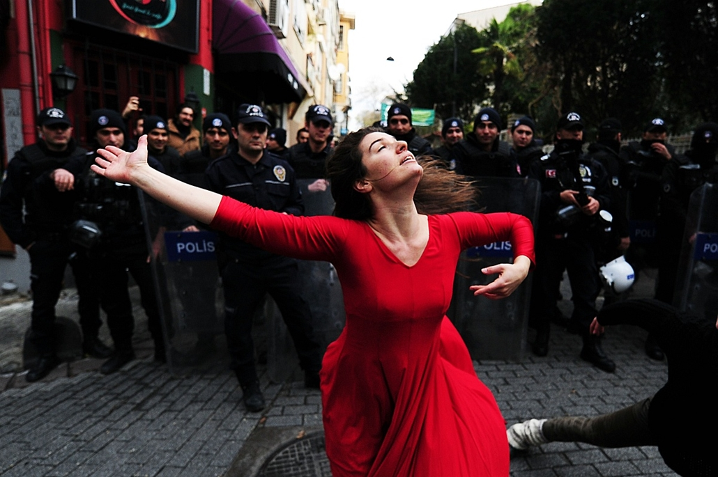 afp. hét képei - Isztambul, Törökország, 2014.12.09. A woman dances in front of riot police during a demonstration on December 9, 2014 in the Kadikoy neighborhood of Istanbul against the eviction of a squatted building. An abandoned building was squatted