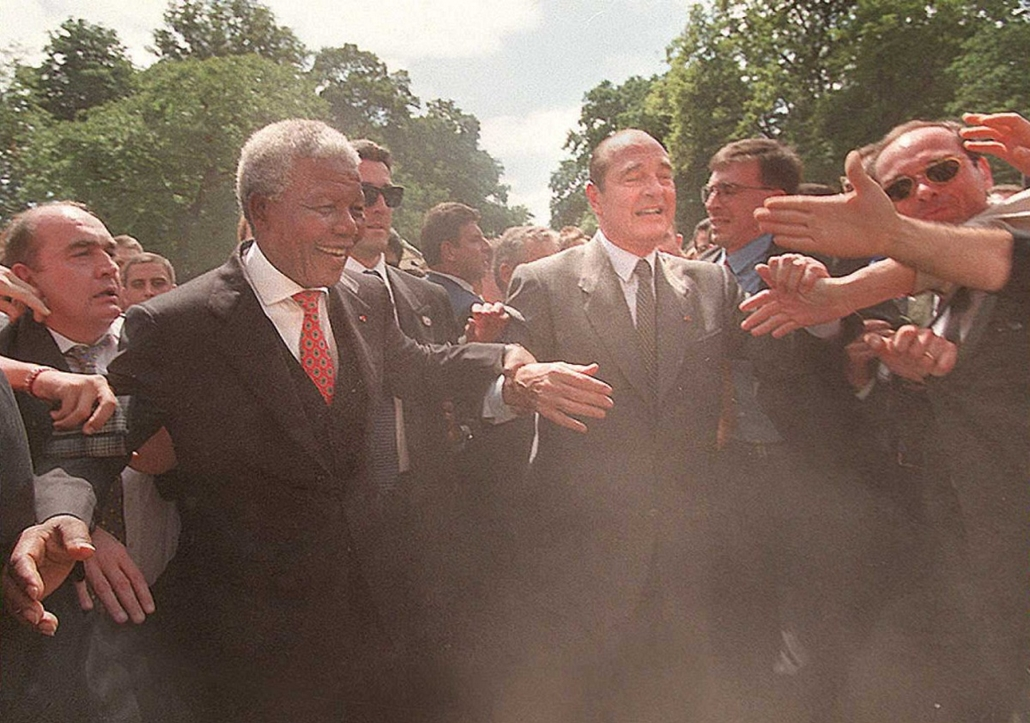 Nelson Mandela nagyítás - FRANCE, Paris : South African President Nelson Mandela (C-L) and his French counterpart Jacques Chirac (C-R), protected by bodyguards, try to find their way through a cloud of dust and the crowd of guests at the traditional Basti