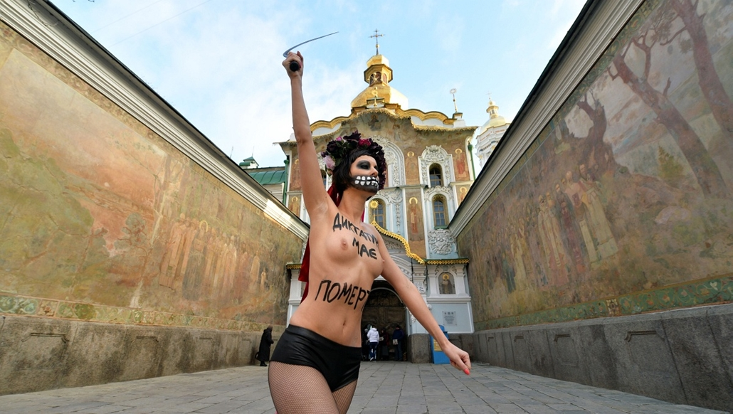 """afp. nagyításhoz - ne használd - 2013.12.An Ukrainian activist from the Femen feminist movement,  dressed up as the death and bearing the words """"Dictatorship must die"""" on her body, waves a sickle and shouts slogan in Kiev on December 1, 2013, to demand Pr"""