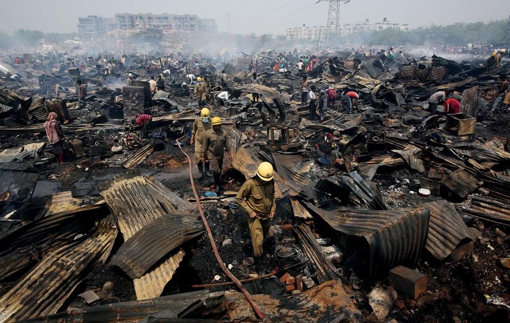 epa. Tűz Újdelhiben 2014.04.25. Tűzoltók a helyszínen, miután tűz ütött ki Újdelhi egyik nyomornegyedében 2014. április 25-én. A tűzvészben mintegy 500 kalyiba vált a lángok martalékává, áldozatokról nem érkezett jelentés
