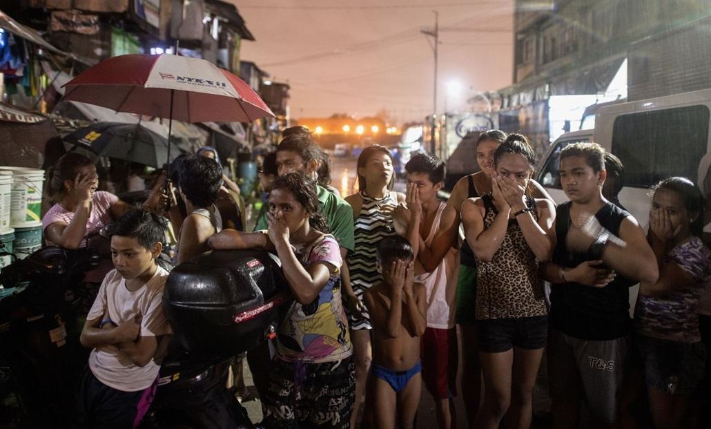 afp.16.09.28. Járókelők nézik a helyszínelőket Manilában, ahol három feltételezett drogfogyasztót ölt meg egy ismeretlen fegyveres férfi