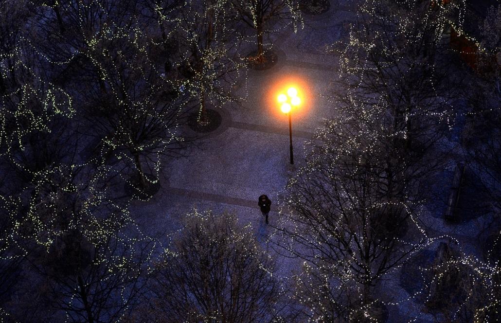 afp.16.11.28. Egy férfi sétál karácsonyi égőkkel díszített fák alatt Prágában, az Óváros téren. karácsony, tél, hideg, fény