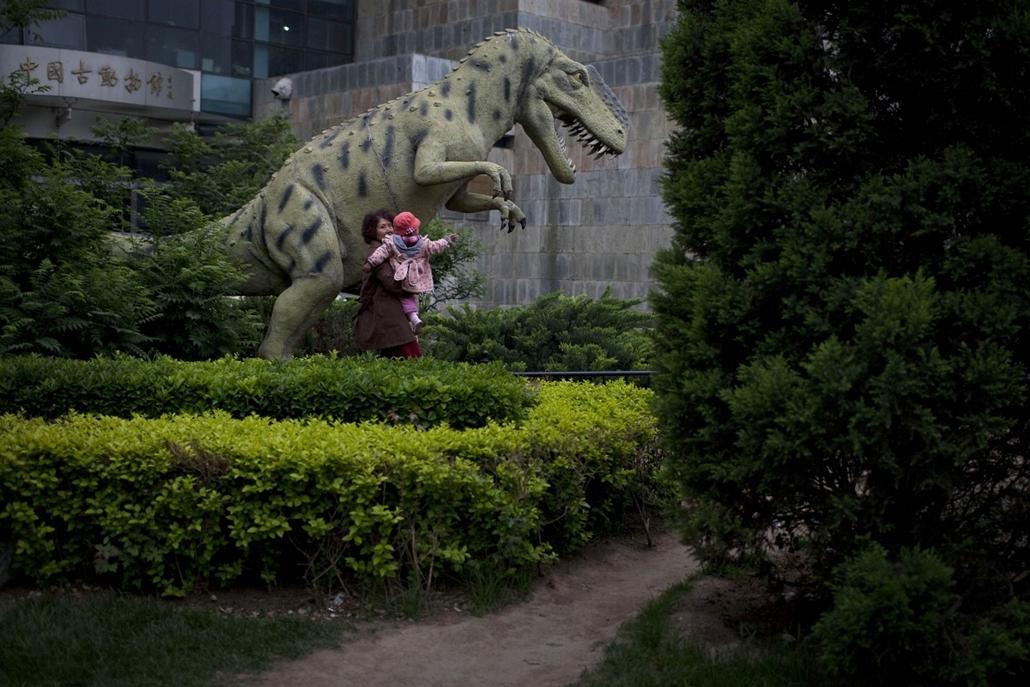 Kína - gyermekét tartó anya a Pekingi Nemzeti Múzeum kertjében.