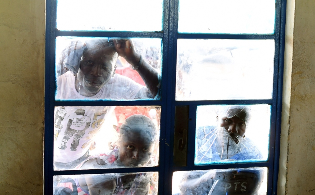 afp. hét képei - Freetown, Sierra Leone 2014.11.11. Relatives of patients at Hastings treatment centre in Hastings, on the outskirts of Freetown, peek inside a building during a ceremony where 63 survivors at the centre were discharged, on November 11, 20
