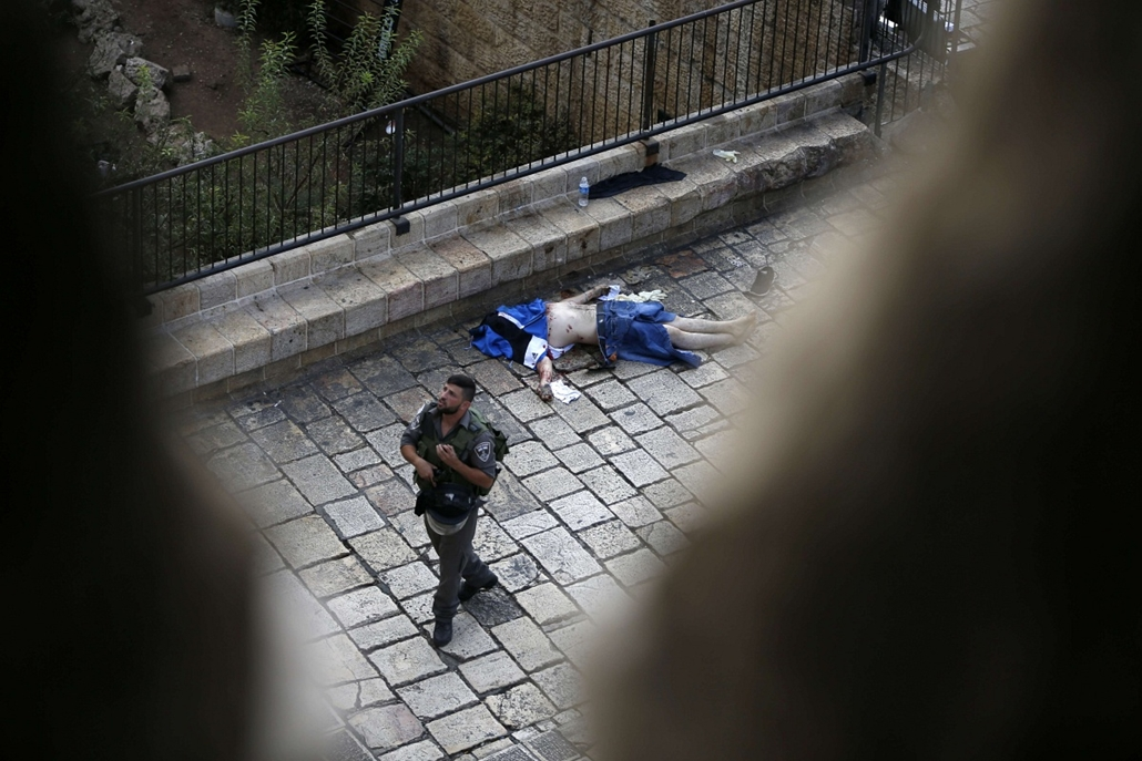 afp.izraeli-palesztin konfliktus 2015 - palesztin támadások Izraelben, 2015.10.10. Jeruzsálem, késelés, An Israeli border guard walks past the body of a Palestinian who was shot dead by Israeli security forces after he stabbed two police officers on Octob