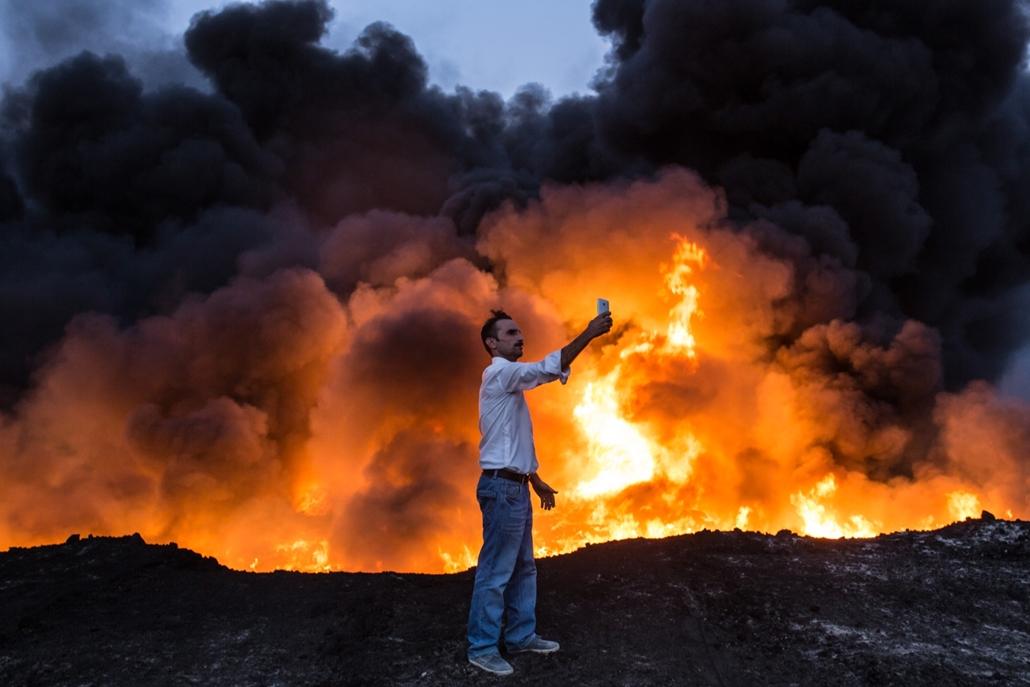 afp.16.10.19. Egy férfi készít szelfit  Qayyarah mellett, háttérben lángolnak az ISIS által felgyújtott olajmezők.