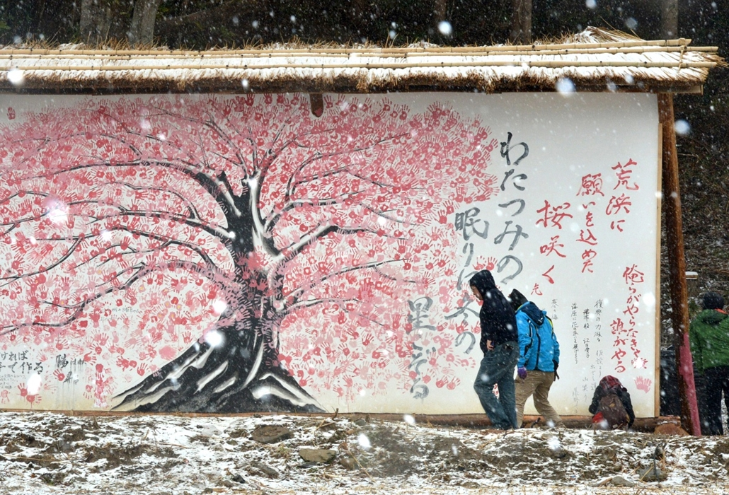 Fák világnapja - JAPAN, Ishinomaki : People look at painting of a cherry tree consisting of the handprints of about 200 people in the disaster-hit Ogatsu district in Ishinomaki, Miyagi Prefecture on Marh 31, 2013. The local residents stamped their hand-pr