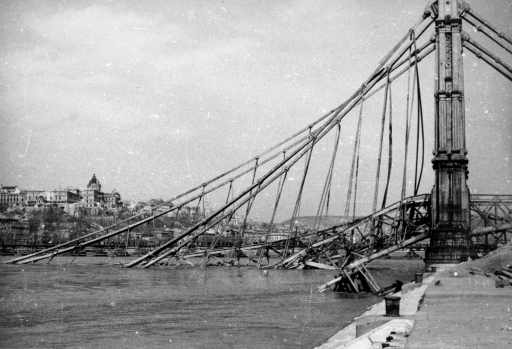 fortepan_! 1945. - A lerombolt Erzsébet híd pesti hídfője az alsó rakpartról nézve, háttérben a romos Királyi Palota. - Erzsébet híd,nagyítás