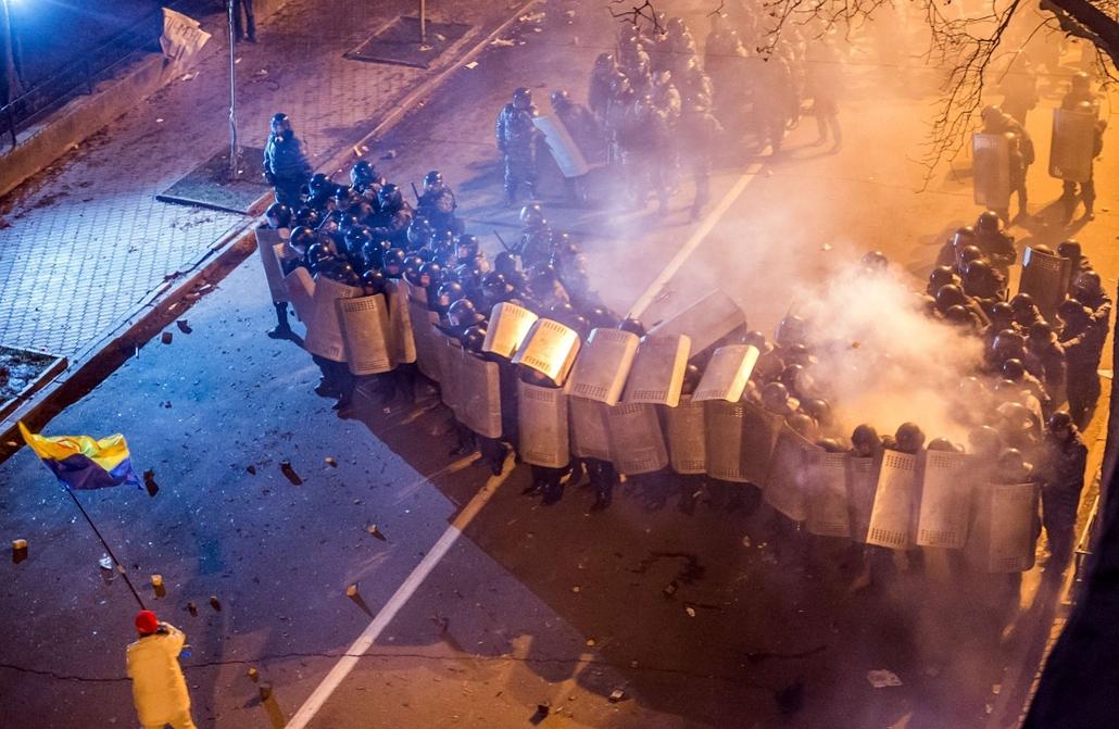 afp. nagyításhoz - ne használd - ukrajna, Kijev, eu, tüntetés, A pro-European Ukrainian demonstrator waves a flag in front of members of the riot police protecting the presidential adminstration office in Kiev as 100 000 outraged Ukrainians swarmed the ci