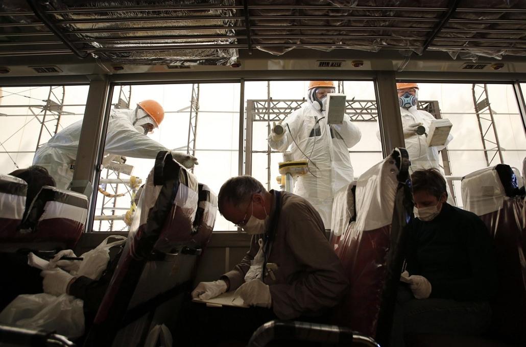 7képei 0308 - Fukusima, 2013. március 6., Munkások sugárzást mérnek egy újságírókat szállító buszon a 2011. márciusi 11-i a Richter-skála szerinti 9-es erősségű földrengésben súlyosan megrongálódott Fukusima-1-es atomerőmű területén a katasztrófa kétéves