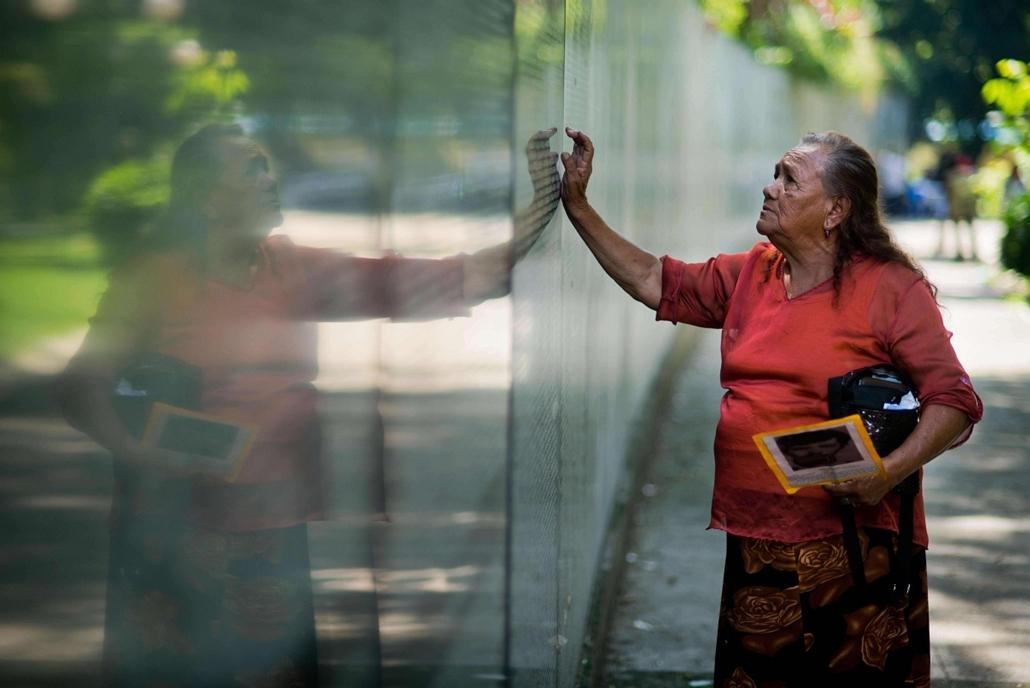 afp. nagyítás - hét képei - 2014.05.27. San Salvador, El Salvador - Salvadoran Estebana Molina looks for the name of a relative at the monument to the people who disappeared during the civil war, at Cuscatlan Park in San Salvador, on May 27, 2014. About 8