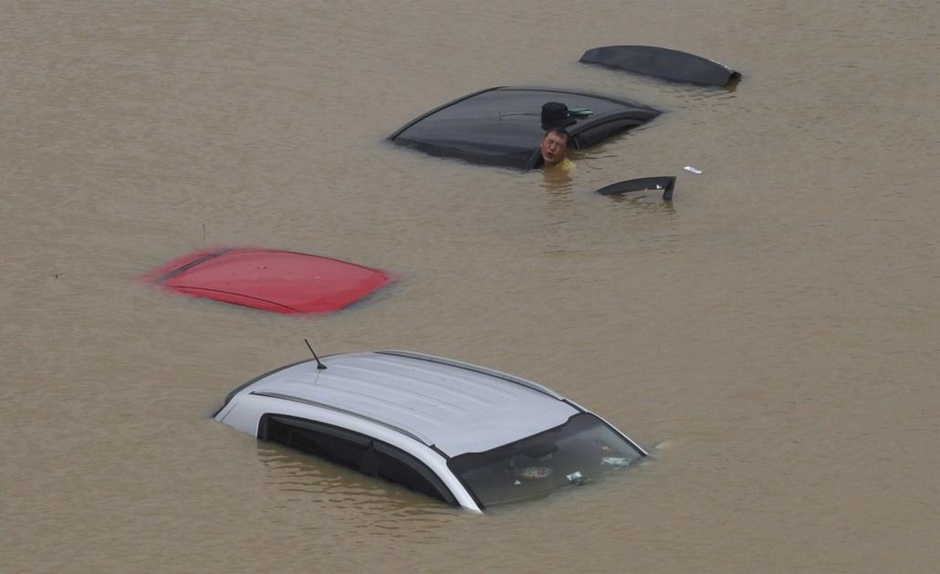 AP!!! augusztus 4-ig!! nagyítás - Egy férfi próbálja megmozdítani járművét Szöul egyik elöntött utcáján 2013. július 22-én, miután heves esőzések következtében nagy mennyiségű csapadék zúdult a Koreai-félsziget középső részére