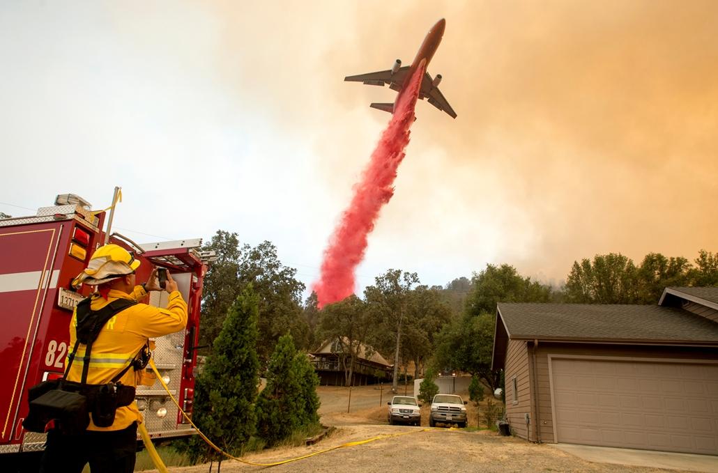 best of 2017  Egy repülő próbálja oltó anyaggal megfékezni a lángokat a ta kalifroniai Mariposa környékén. 45.000 hold erdő vált a tűz martalékává