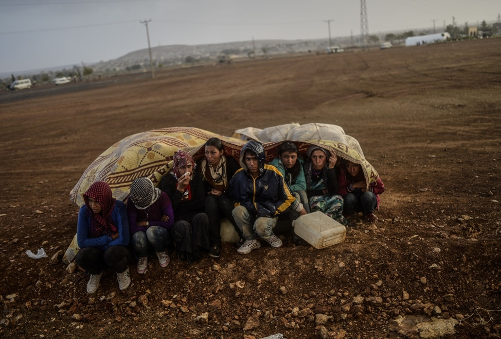 afp. hét képei - Suruc, Törökország, 2014.10.02. Szíriai kurdok, menekültek, Syrian Kurds take cover from the rain in the southeastern town of Suruc in the Sanliurfa province after crossing the border between Syria and Turkey after mortars hit both sides