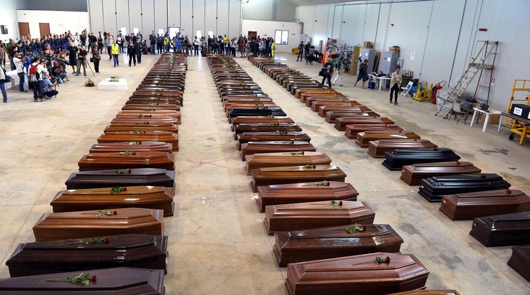 afp. hajóval érkező menekültek, migránsok, - Lampedusa, Olaszország, 2013.10.05. Coffin of victims are seen in an hangar of Lampedusa airport on October 5, 2013 after a boat with migrants sank killing more than hundred people. Italy mourned today the 300