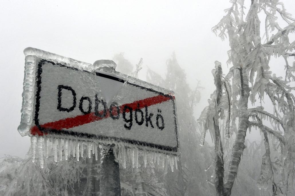mti. ónos eső, jegesedés, tél 2014, 2014.12.02. Pilisszentkereszt, Jég borítja a település helységnévtábláját a Dobogókőre vezető úton 2014. december 2-án. A katasztrófavédelem és a rendőrség lezárta az utat az ónos esőtől kialakult eljegesedés miatt, a t