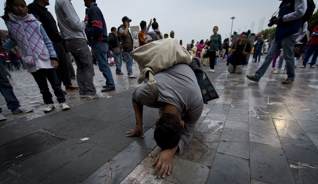 afp. hét képei - Mexikóváros, Mexikó, 2014.12.11. A young exhausted pilgrim on his knees arrives with other devoted Catholics at the esplanade of the Guadalupe Basilica after a long and painful procession in Mexico City on December 11, 2014 before the bir