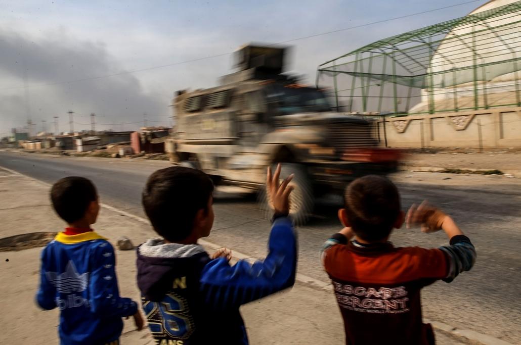 afp.16.11.08. Gyerekek integetnek az úton elhaladó pesmega harcosoknak Mosul mellett.